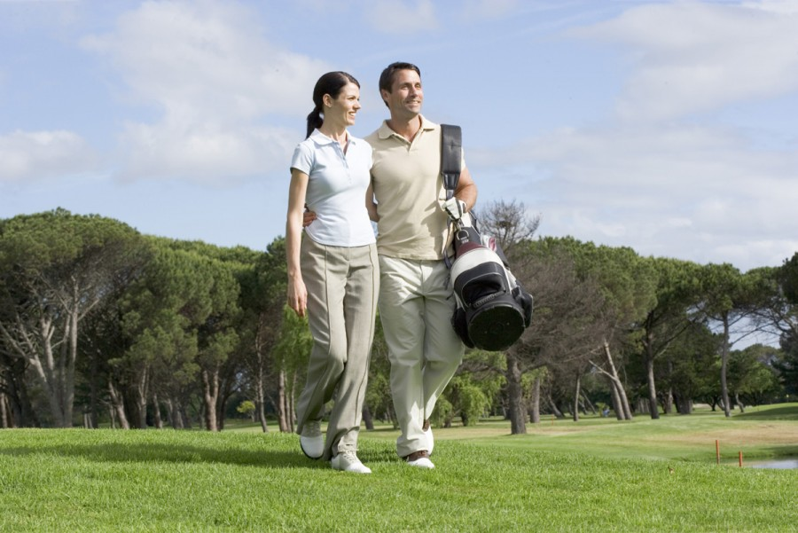 Couple with golf clubs walking on golf course