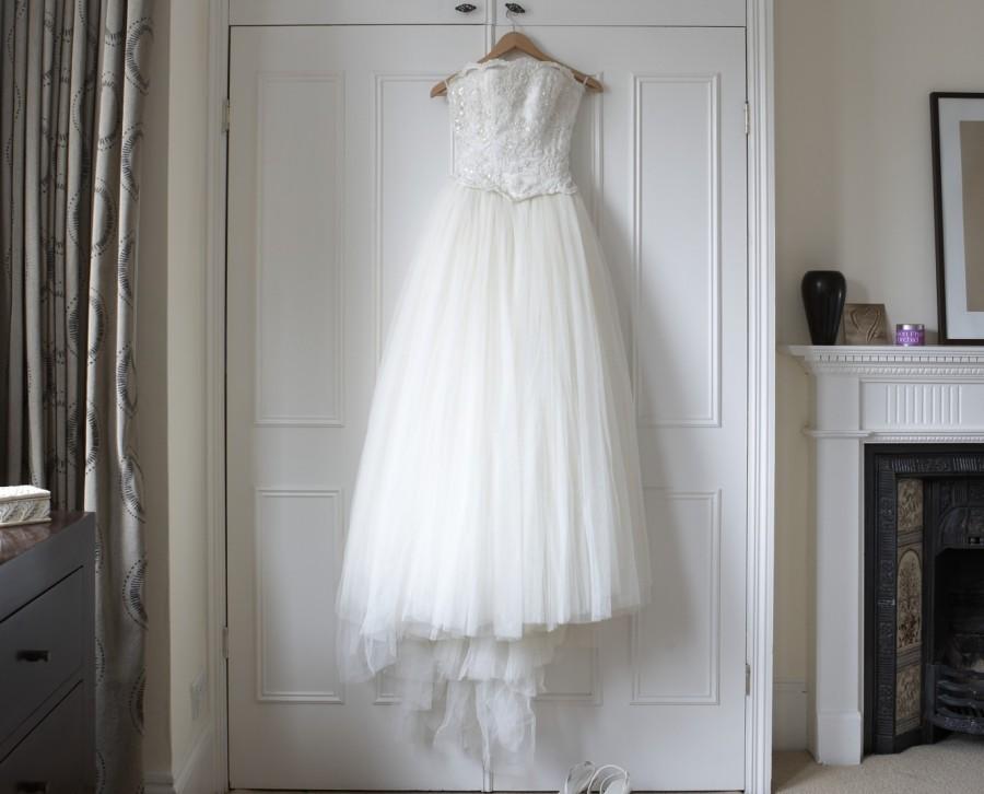 Wedding dress hanging on wardrobe doors, white shoes on floor