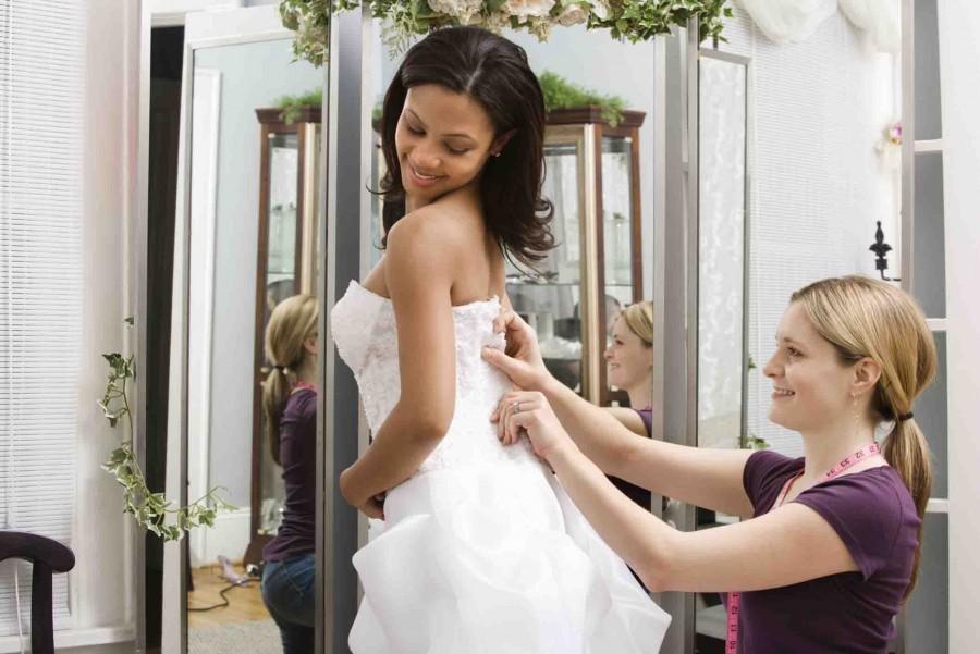 Caucasian seamstress helping African-American bride in bridal shop.