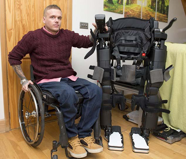 Ben is wheelchair bound after a car accident in 2011 which left him paralysed. He now has the REX walking machine to help him stand and walk. Image Mirrorpix via Daily Mail