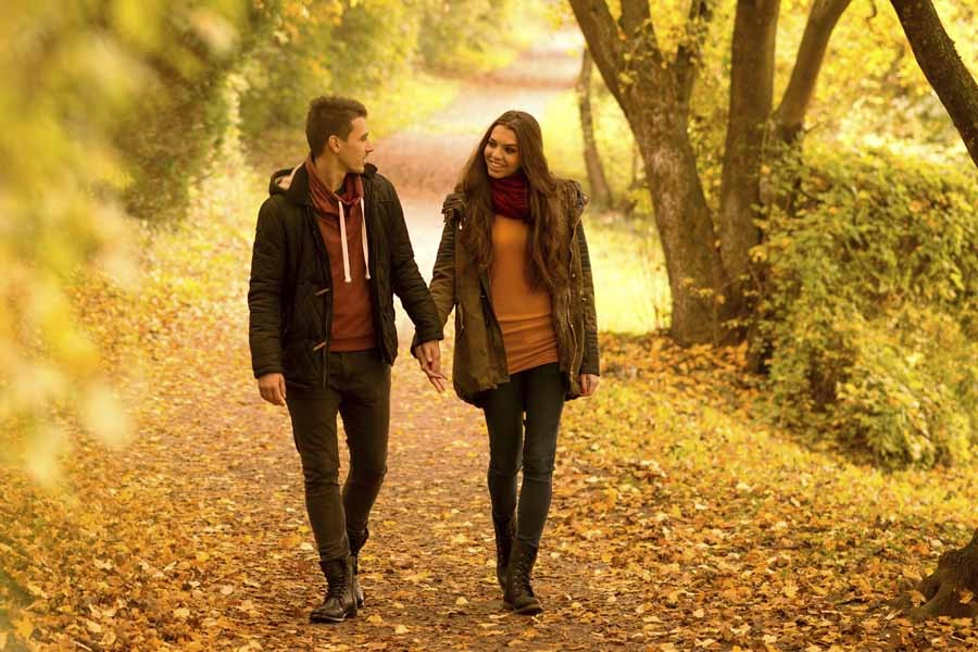 Lovers walking holding hands in autumn park