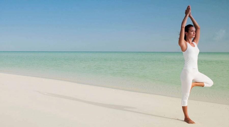 woman doing yoga on a sandy beach