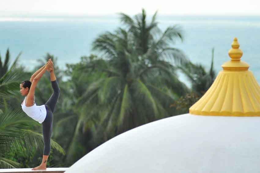 woman doing yoga on the rooftop in thailand