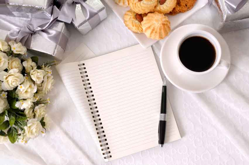 Folded notebook and pen laid on bridal lace with several silver wedding gifts and fabric rose bouquet, with cup of coffee and biscuits.
