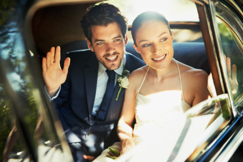 Shot of a newlywed couple looking out the window of a car and waving